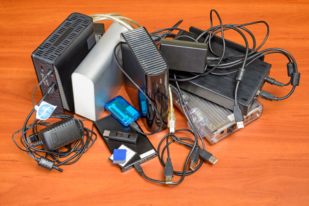 entangled: Many memory devices like hard disk drives or memory cards, in format USB or Firewire, with a lot of entangled cables Stock Photo