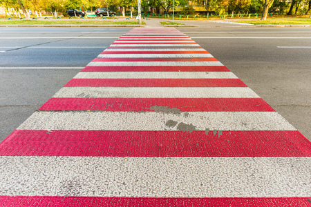 pedestrian crossing: A red and white pedestrian crossing on blue black asphalt in the town of Kiev, Ukraine Stock Photo