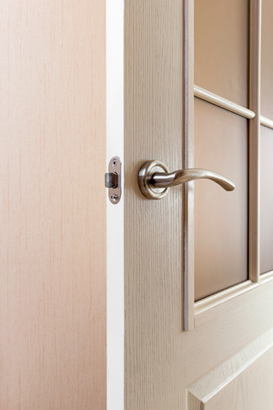 glass door: Detail of a modern style satin nickel handle on a white glass door Stock Photo