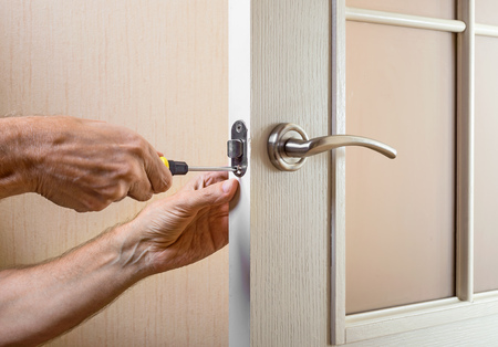 deadbolt: A man is mounting the protection strike of the deadbolt on a glass door with a modern curved style nickel handle using a screwdriver