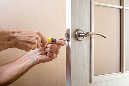 glass door: A man is mounting the protection strike of the deadbolt on a glass door with a modern curved style nickel handle using a screwdriver