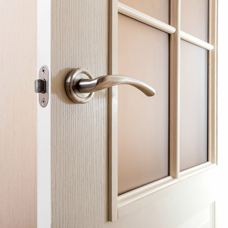 deadbolt: Detail of a modern style satin nickel handle on a white glass door Stock Photo