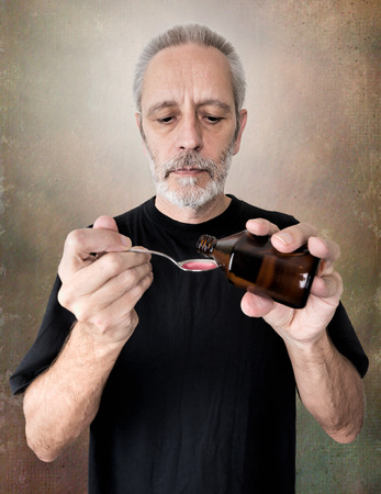 sore throat: A mature man is pouring cough syrup in a spoon to cure his sore throat and bronchitis Stock Photo