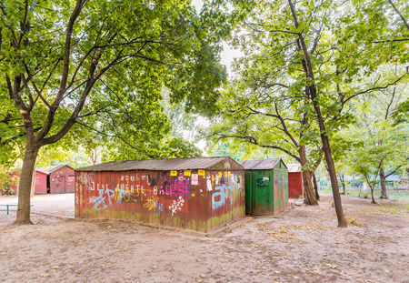 worn structure red: KievUkraine - September 19, 2015 - Old rusty garage under the tree with graffiti in cyrillic, in the Obolon district