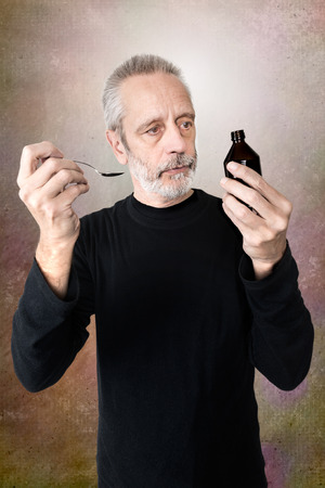 bronchitis: A mature man is pouring cough syrup in a spoon to cure his sore throat and bronchitis Stock Photo