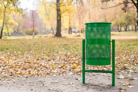 New green trash bin in the park in autumn