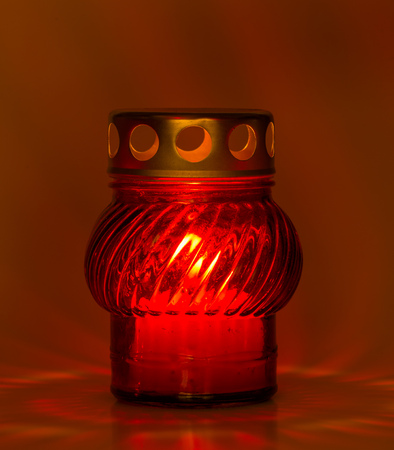 tea light: A red glass tea light with a candle inside to illuminate the Xmas night and other celebrations Stock Photo