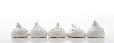 aligned: Five white french meringues aligned in a row, isolated on white background