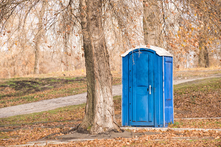 Blue outdoor chemical toilet in the park in winter Banco de Imagens