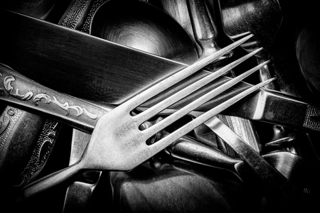 Abstract black and white photo of mixed silver forks, spoons and knives Stock Photo