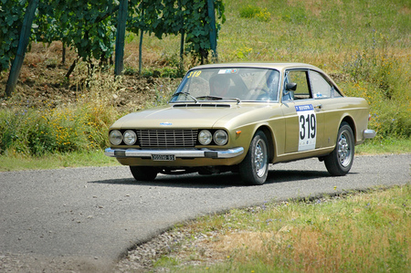 fiat: Cremona  Italy -  September 7, 2005 - Unidentified drivers on a gold vintage Fiat 124 coupe racing car