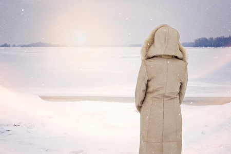 fur hood: A woman with a leather coat with a fur hood is looking at the frozen Dnieper river during a cold and sad gray winter morning under the snow