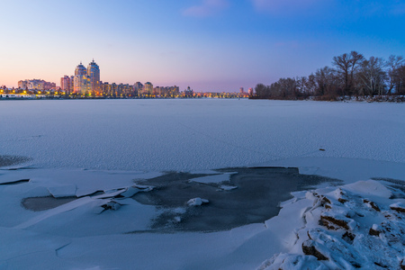appears: Cold Winter night cityscape with illuminated buildings in Kiev, Ukraine. The frozen Dnieper river appears in the foreground Stock Photo