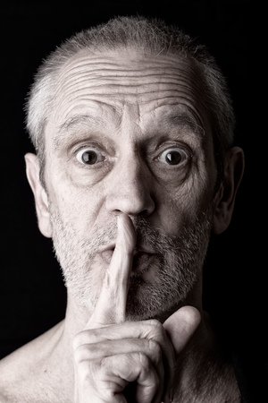 shush: Portrait of an attractive adult man putting the finger in front of the mouth and saying Hush! Stock Photo