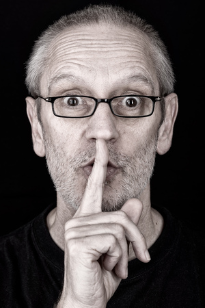 shush: Portrait of an attractive adult man, wearing glasses, putting the finger in front of the mouth and saying Hush! Stock Photo