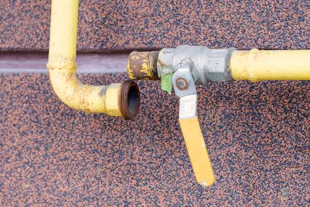 Un tube de gaz jaune cassé, avec un robinet, à l'extérieur d'une maison à canaliser l'énergie douce à la maison. Banque d'images - 54405476