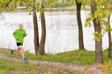 one people: A senior man worn in black and green is running in the park, close to the lake, during a gray spring day