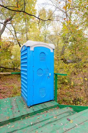 Blue outdoor chemical toilet in the woods in autumn