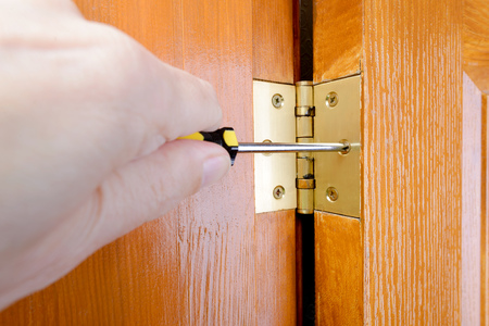A man is using a screwdriver to adjust a Door hinge Stock Photo