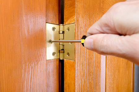 A man is using a screwdriver to adjust a Door hinge 스톡 콘텐츠