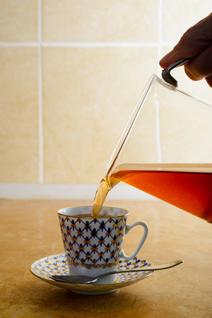 Pouring hot coffee in an elegant porcelain cup, in the kitchen