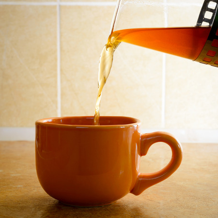 Pouring hot tea in an orange porcelain cup, in the kitchen Stock Photo