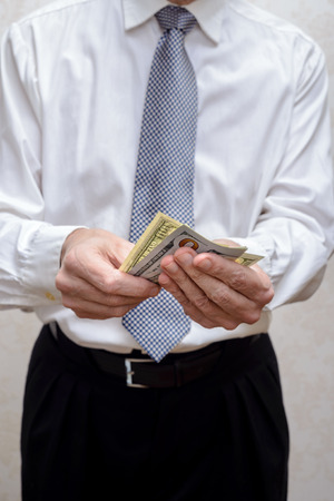 corrupted: Corrupted businessman, or politician, counting and offering a Dollar banknotes bribe Stock Photo