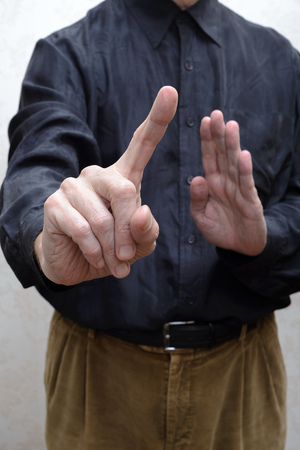 corrupted: A man saying stop or no with a finger gesture. Refusing to take the bribe from corrupted people