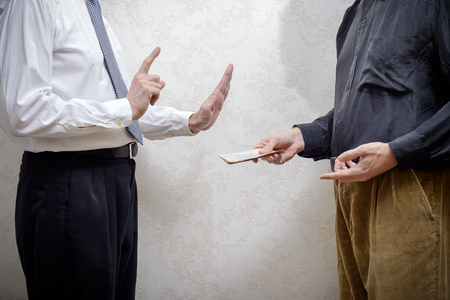 corrupted: Corrupted man offering a Hryvnia banknotes bribe to a businessman, or politician, rejecting any kind of corruption, in Ukraine