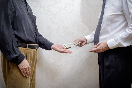 corrupted: Corrupted businessman, or politician, paying a Dollars banknotes bribe to a man accepting corruption