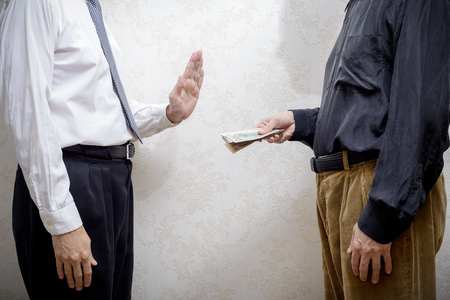 corrupted: Corrupted man offering a Dollars banknotes bribe to a businessman, or politician, rejecting any kind of corruption