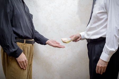 corrupted: Corrupted businessman, or politician, paying a Hryvnia banknotes bribe to a man accepting corruption, in Ukraine