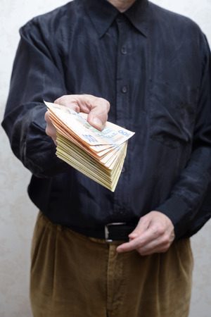 corrupted: Corrupted businessman, or politician, offering a Hryvnia banknotes bribe, in Ukraine