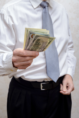 corrupted: Corrupted businessman, or politician, offering a Dollar banknotes bribe Stock Photo