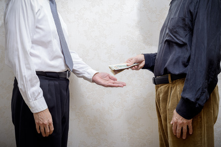 corrupted: Corrupted man paying a Dollars banknotes bribe to a businessman, or politician, accepting corruption