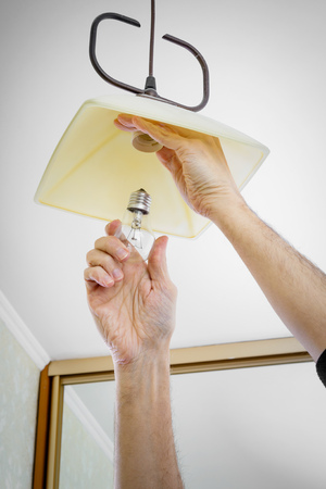 electric fixture: Man installing or changing a bulb, fixing it to the socket at home