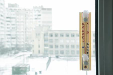 adentro y afuera: Un termómetro, fijado fuera de la ventana, muestra que es menos diecisiete grado celsius al aire libre, mientras que es cálido dentro de la habitación