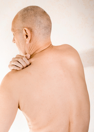 displacement: Man massaging his top back, the trapezius muscle, because of a thoracic vertebrae pain due to a displacement of a dorsal vertebra rubbing on a nerve