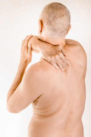 Man massaging his top back, the trapezius muscle, because of a thoracic vertebrae pain due to a displacement of a dorsal vertebra rubbing on a nerve