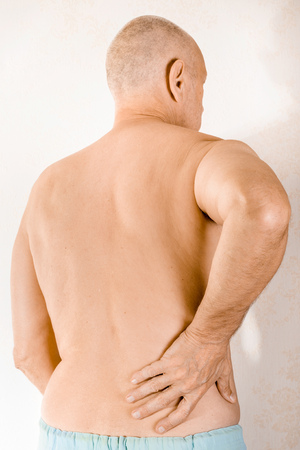 displacement: Man massaging the low back because of a painful lumbago due to a displacement of the lumbar vertebrae