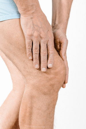 elongacion: Athlete man massaging a painful  quadriceps and the knee after a sport accident. It could be a quadriceps tendinopathy, a muscle elongation, a medial meniscus tears or bursitis