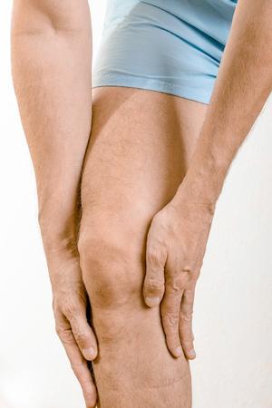 elongacion: Hombre deportista masajeando un doloroso músculo sóleo y gastrocnemio, debajo de la rodilla, después de un accidente deportivo. Podría ser un claquage musculaire o una elongación muscular