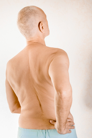 Man massaging the low back because of a painful lumbago due to a displacement of the lumbar vertebrae