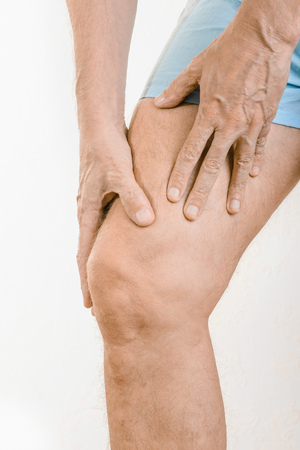 elongacion: Athlete man massaging a painful  quadriceps after an accident. It could a musculaire claquage or a muscle elongation
