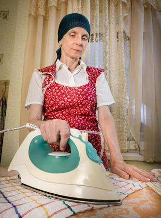 iron curtains: An adult woman, a housewife or a maid, with a green scarf on the head and wearing a red apron, is standing behind the ironing board. She irons some tea towels in the kitchen