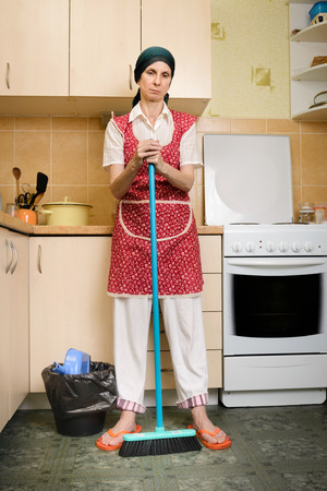 A depressed  adult woman, a housewife or a maid, wearing a red apron and a green scarf on her head is resting after she has swept the kitchen with a broom