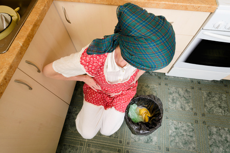 A woman, with a scarf on the head and a red apron, is looking inside a black trash can with a garbage bag, in the kitchen. She is very disturbed by the bad smell