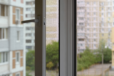 Open window with a mosquito screen to prevent insects and bugs, like flies, bees, mosquitoes or wasps from entering Stock Photo