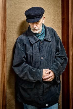 Portret van een volwassen man met een witte baard en een pet op het hoofd. Hij zou een zeeman, een arbeider, een havenarbeider of zelfs een gangster of een misdadiger kunnen zijn. Hij heeft een indringende blik.