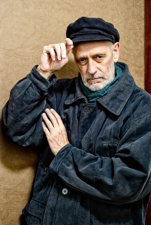 Portrait of a mature man with a white beard adjusting his cap on the head. He could be a sailor, a worker, a docker, or even a gangster or a thug. He has a penetrating gaze. Stock Photo